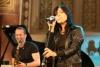 Die Sängerin Stefanie Kloß singt während eines Konzerts, im Hintergrund ist David Klein zu sehen, diesmal aus einem anderen Winkel